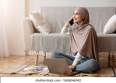 Work Opportunities For Muslim Women Concept. Smiling Arabic Girl In Hijab Talking On Cellphone And Using Laptop While Sitting On Floor At Home.