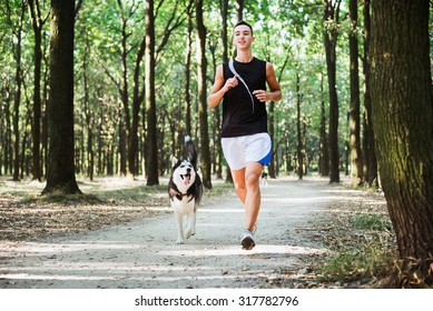 work out with dog. Young caucasian male running with siberian husky dog. Man and husky jogging in park