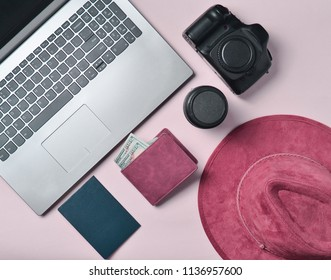 Work of the photojournalist. Laptop, wallet, passport, hat, camera, lens. Travel concept, top view, flat lay