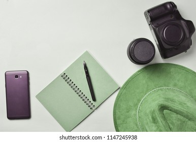 Work of the photojournalist. Smartphone, notebook, hat, camera, lens. Travel concept, top view, flat lay
