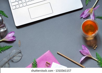 Work place concept flat lay with spring flowers, a keyboard and a cup of tea. Top view business card. Copy space