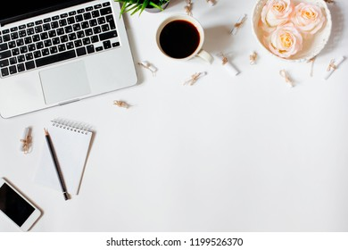 Work place in flat lay style. Cute modern white office desk table with laptop, smartphone, office plant, roses in vintage tray, notebook, sunglasses, pen and pencil. Top view with copy space, flat lay