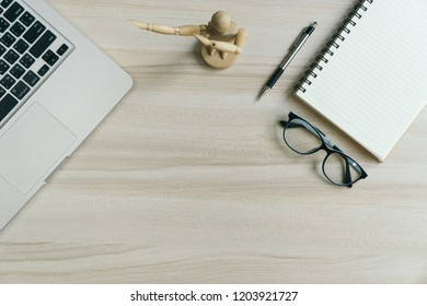 Work place in flat lay style. modern white wood office desk table with laptop, glasses, wooden doll, notebook, pen and pencil. Top view with copy space, flat lay