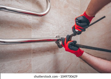 The work plumber inaccurately mounts a wrench with a new chrome-plated heated towel-type coil on the wall of the tile