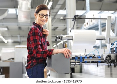 Work in the printing house. The woman supports a foil for printing.