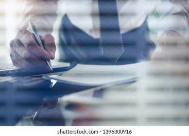 Work process concept. Businessman using calculator to calculate accountancy document with laptop computer on desk. Man executive manager hand holding a pen working with blind in modern office