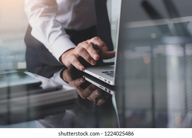 Work process, corporate performance management concept. Businessman, man project manager working on laptop computer in modern office with mobile phone, digital tablet, notebook on desk, close up