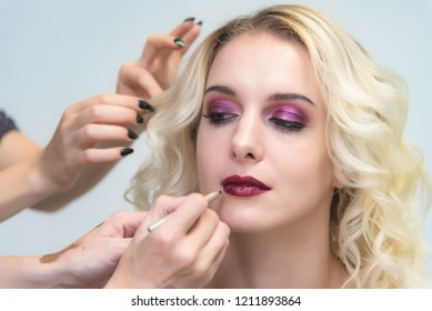 The work of a professional makeup artist - beautician, makes makeup with a brush on the face of a beautiful blonde on the lips of a model. Makeup artist creating beautiful makeup for blonde model