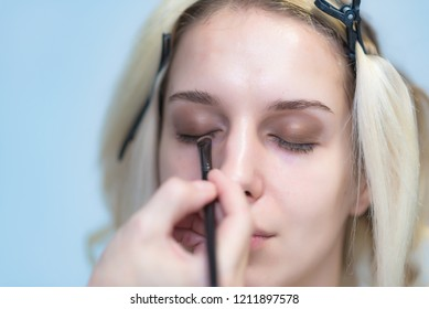 The work of a professional makeup artist - beautician, makes makeup with a brush on the face of a beautiful blonde with shadows on the eyes of the model. Painting of eyebrows.