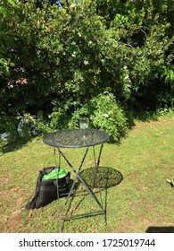 Work in progress in the garden - An empty glass on a small garden table and an open tool bag on the lawn