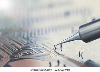 Work in progress. Soldering of electronic circuit board with electronic components. Soldering station. Engineers repair circuit board with soldering iron.