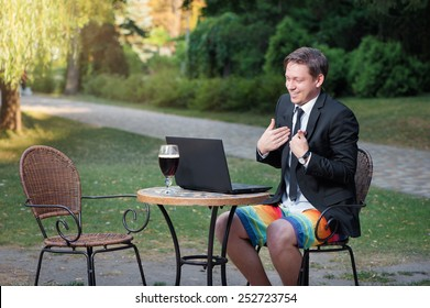Work and relax. Online conference. Businessman dressed in suit and shorts working with laptop, talking by skype at the park cafe outdoors