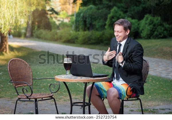 Trabalhe e relaxe. Conferência online. Empresário vestido de terno e shorts trabalhando com laptop, falando por skype no café do parque ao ar livre