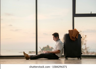 Work remote. Handsome young man with suit working and typing on laptop while sitting on the floor leaning on suitcase near big window at airport and Background beautiful sunset. Selective focus