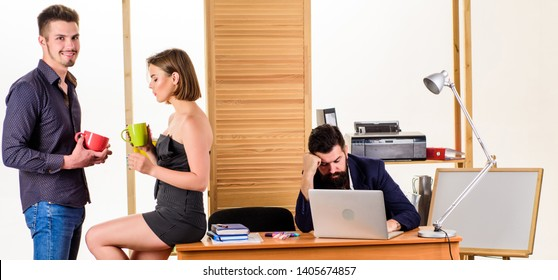 Work and rest balance. Young coworkers enjoying rest break at work. Pretty woman and handsome man having rest in office while colleague working in background. Managers drinking tea in rest hour.