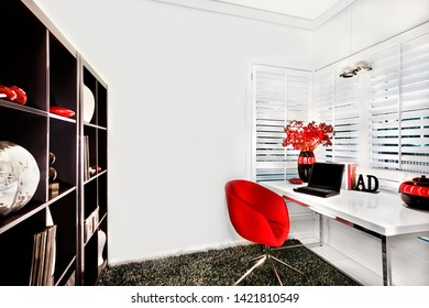 Work room walls are white and floor has a wool carpet. The chair is red. A wooden shelf with items, the table is white near to the window. A laptop and shiny vases with flowers.