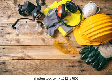Work safety. Construction site protective equipment on wooden background, flat lay, copy space, top view