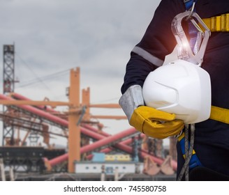 A work safety officer or a civil engineer, A white helmet and a seat belt, coupled with a blurred industrial background, Close up of man in suit with construction  and gloves in hand
