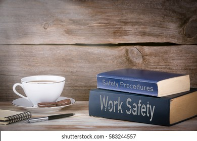 Work Safety and Safety Procedures. Stack of books on wooden desk