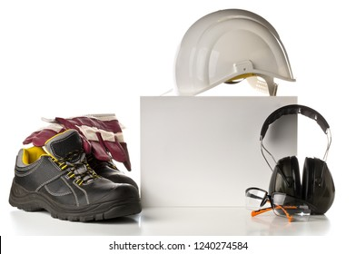 Work safety and protection equipment - protective shoes, safety glasses, gloves and hearing protection over white background with blank card for copy