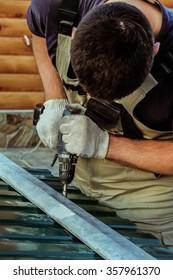 Work screwdriver. Worker fastens screwdriver steel sheet coating to the steel frame.