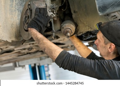 Work in the service station, suspension repair, CV joint removal.