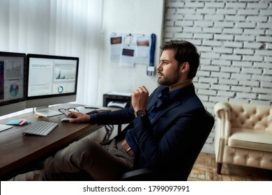 At work. Side view of young successful businessman or sales manager analyzing financial data on computer, looking at statistics on pc screen while sitting at his workplace in the modern office