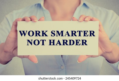 Work Smarter Not Harder Concept. Closeup retro style image business woman hands holding card with motivational message phrase text written on it isolated grey office wall background