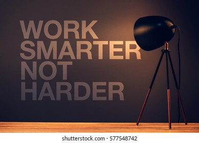 Work smarter not harder, motivational quote on office wall illuminated with desk lamp