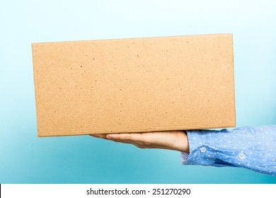 Work social life balance. Woman holding a cardboard box with her hand with empty space for text.