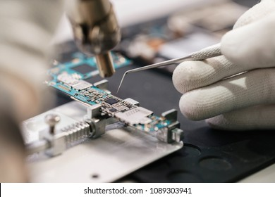 Work with a soldering iron. Microelectronics device. Close-up hands of a service worker repairing modern smartphone. Repair and service concept.