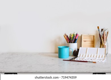 Work space Artist or designer Mock up : Desk space  or tabletop with brush, color pencil and craft tools. desk with copy space for products display montage.