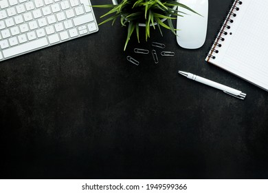 Work space with black desk and keyboard, plant, mouse, note pad and pen - top view, copy space