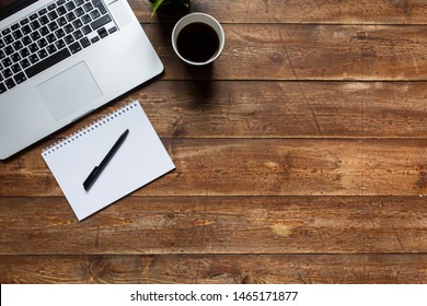 work space of a businessman. view from above . coffee black note and laptop on the desktop with black note. laptop on wooden background