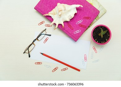 Work space with empty sheet,pins,pencil,pink note books,plant.Business concept.Top view