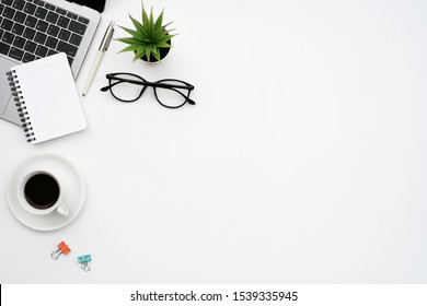 Work space office business and finance concept on white table desk background with laptop computer and coffee cup, green plant and glasses, Top view with copy space, flat lay