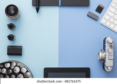 Work space on blue table of a creative designer or photographer with laptop, camera other objects of inspiration and copy space. Stylish home studio concept of technology trends. View from above.