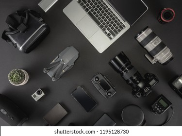 Work space photographer with laptop, digital camera, memory card, action camera, drone, remote controller, phone, VR glasses and accessory. Top view on black table background.  Mockup template