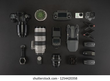 Work space photographer with laptop, digital camera, memory card, action camera, drone, remote controller, phone and camera accessory. Top view on black table background. Concept of mockup template.