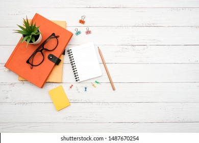 Work space school desktop concept on white wooden table desk with blank notepad and stack of book , glass, pencil, green plant and paper clip, flat lay, Top view with copy space