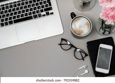 Work space table with laptop, phone and coffee on grey background. Top view, Flat lay