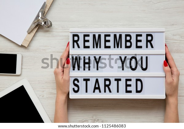 Work space with tablet, smartphone, sheet and 'Remember why you started' words on lightbox on white wooden table. Female hands hold modern board with text. Top view, flat-lay, overhead.