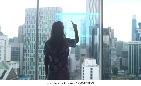 Work of an IT specialist woman before which a hologram of the problem is being developed, against the backdrop of modern office buildings.