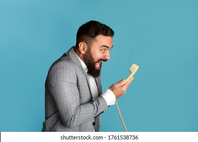 Work stress concept. Angry businessman shouting into landline phone receiver against blue background