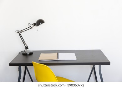 work table with book lamp and yellow chair at home