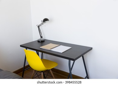 work table with book, lamp and yellow chair at home