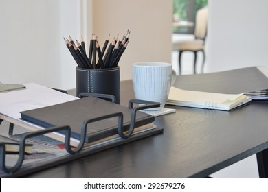 work table with book,pencils and cup of coffee and in a home