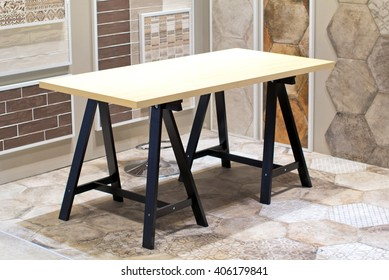 Work table in the room, wooden board on the sawhorse in an empty room