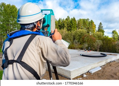 Work with a tachometer. Topographic survey. Gyodetic work during construction. A man with a tachometer next to the foundations. Concept - career of a giadesist. Foundation check. Equipment.