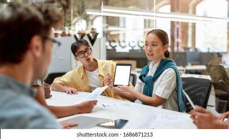 Work in team. Young asian woman showing tablet to her colleagues and discussing something while working together in the modern office. Business meeting. Team building concept